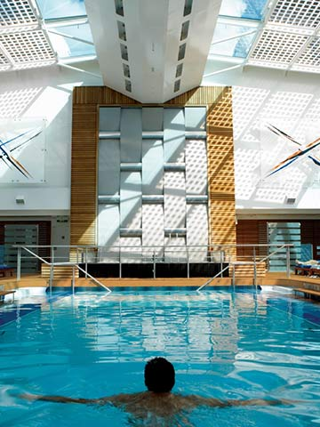 Man swiming in the Solarium Pool on-board Celebrity Equinox